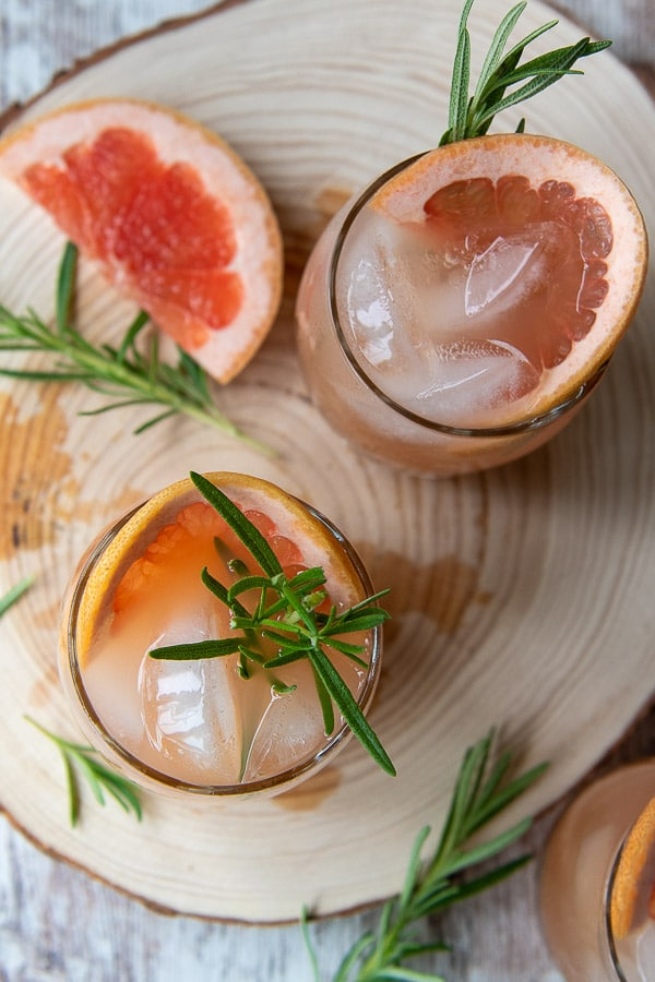 overhead shot of grapefruit cocktails on a wooden board
