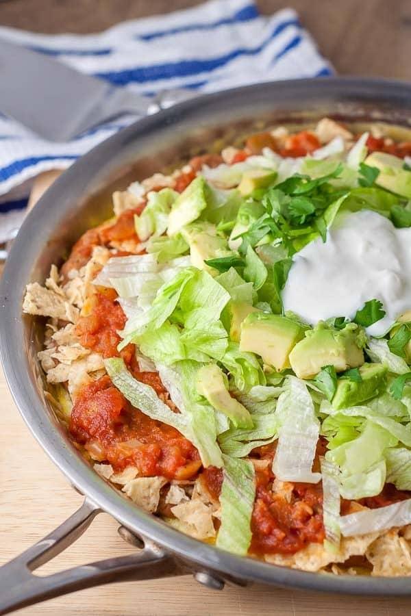 Mexican frittata shown in a saute pan layered with lettuce, avocado, salsa, cilantro, and sour cream