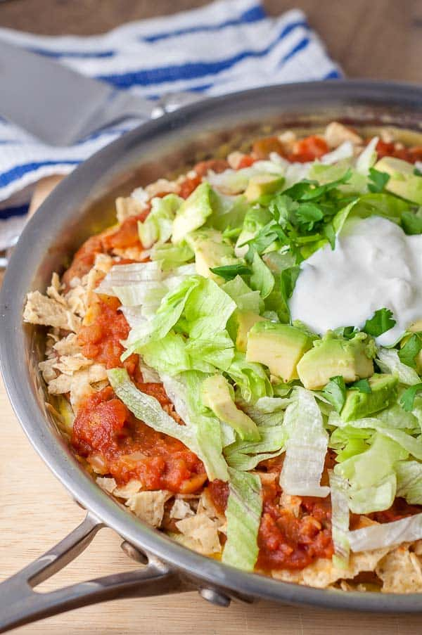 Mexican frittata shown in a saute pan layered with lettuce, avocado, salsa, cilantro, and sour cream