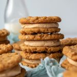 a stack of three cookie sandwiches with a milk bottle in background