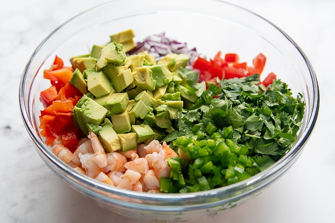 ingredients in a glass bowl to make mexican shrimp ceviche