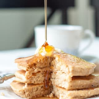 a stack of Fluffy Flourless Banana Oatmeal Pancakes with syrup being poured on