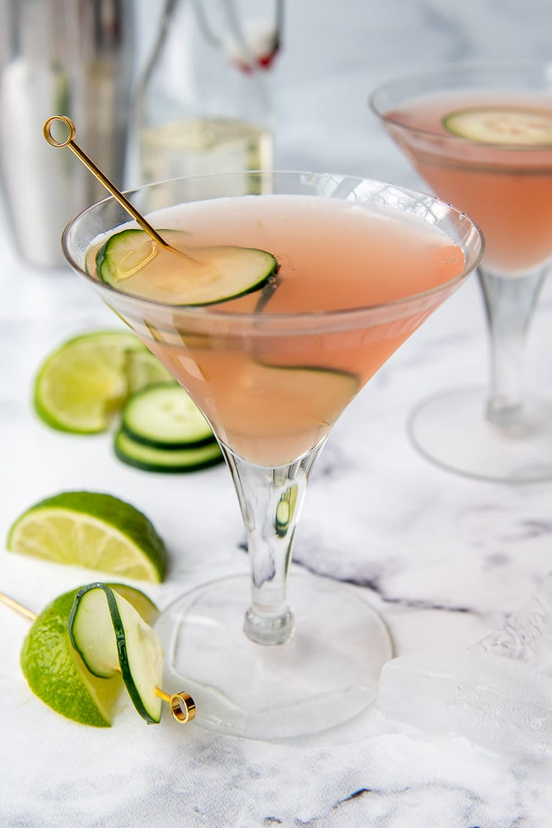 a pink cucumber cosmo with another drink and martini shaker in the background