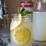 straight on shot of spiked lemonade with sliced lemons in a jar glasses