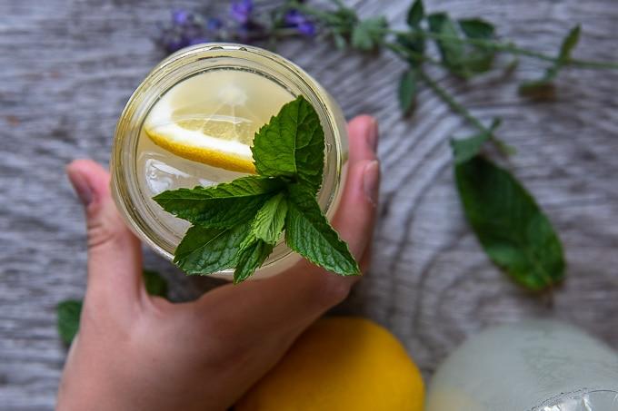 overhead shot of a hand grabbing a vodka lemonade with fresh mint garnishing glass