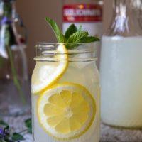 straight on shot of spiked lemonade with sliced lemons in a jar glasses