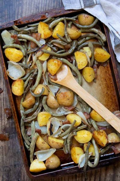 overhead shot of a baking sheet with roasted potatoes and green beans with a wooden spoon resting on it