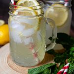 lemon shake-up in jar glass on a wooden circle with red and white straws