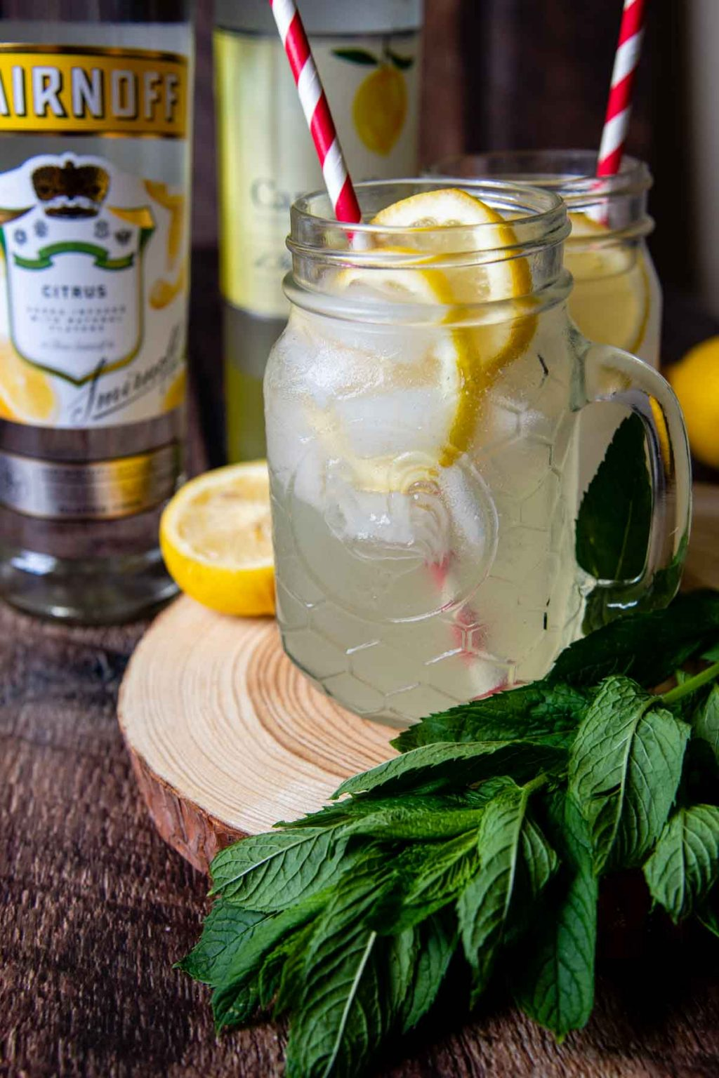 two lemon shake-ups with citrus vodka and limoncello in the background
