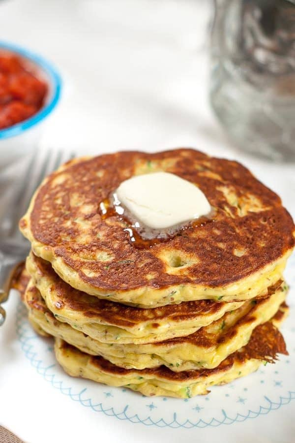 A stack of gluten free zucchini pancakes on a white plate with a pad of melting butter on top
