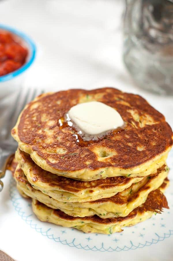 A stack of easy, gluten free zucchini pancakes on a white plate with a pad of melting butter on top
