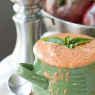 a bowl of cream of tomato soup dripping over the side with fresh basil floating on top