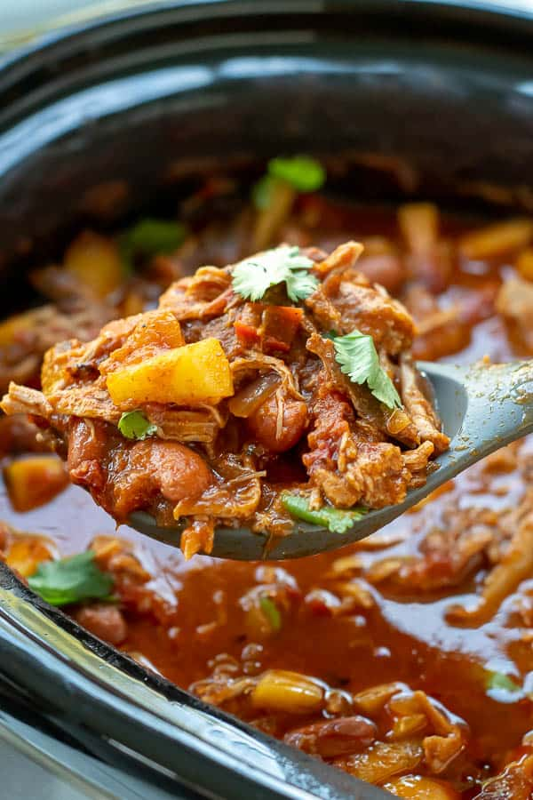 a large serving spoon lifting pork chili out of a slow cooker