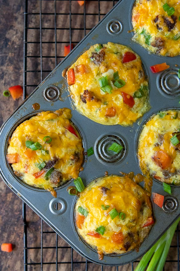 breakfast egg muffins in muffin tins with chopped pepper around