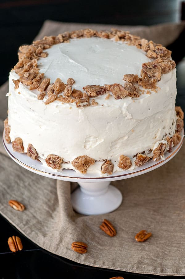 "Pumpkin Praline ""PieCaken"" Cake on a cake stand with pecans drizzled underneath"