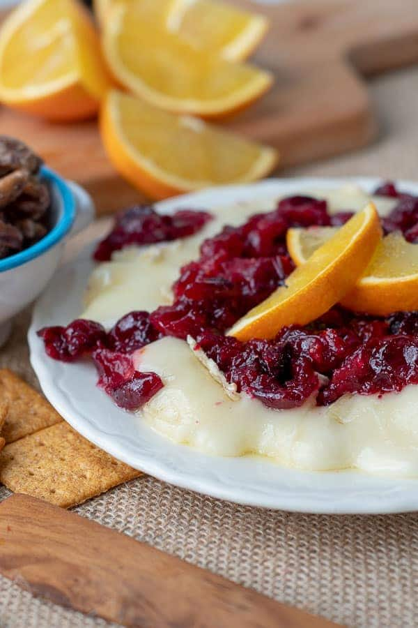a white plate with cranberry baked brie and sliced oranges on top