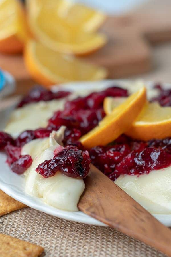 a wooden knife cutting into cranberry baked brie