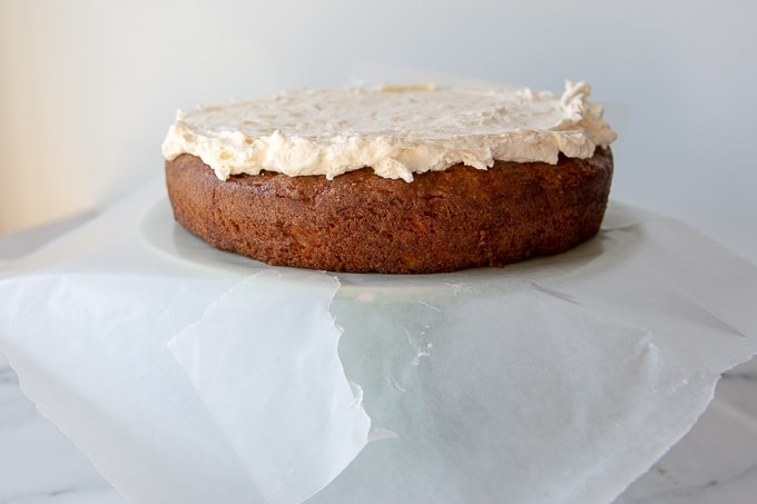 one layer of carrot cake with pineapple on a cake stand getting frosted