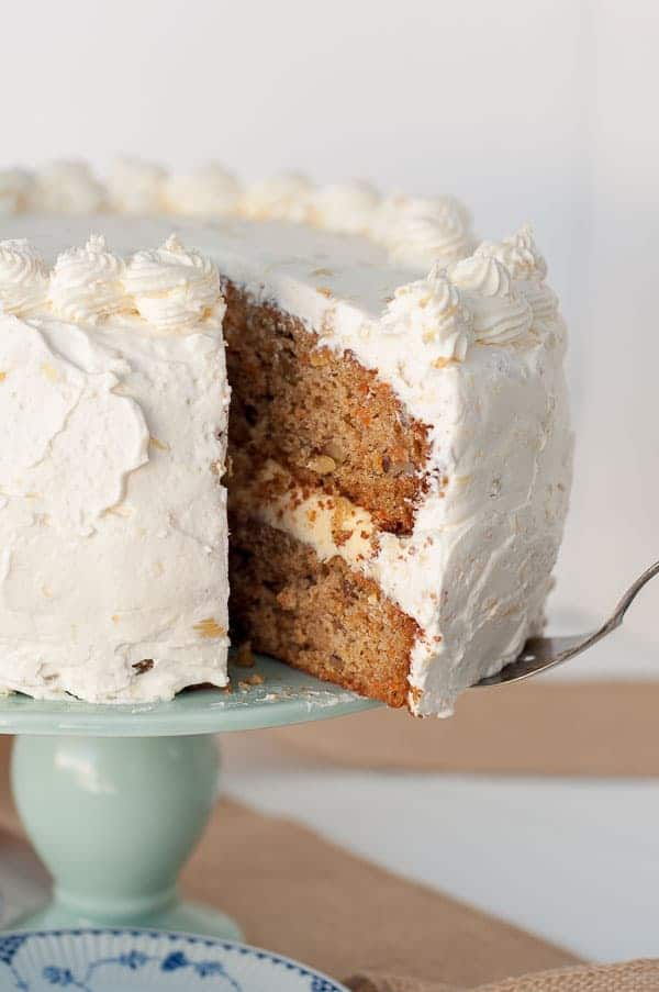 A big slice being taken out of Pineapple Carrot Cake with Fluffy Pineapple Whipped Cream Frosting