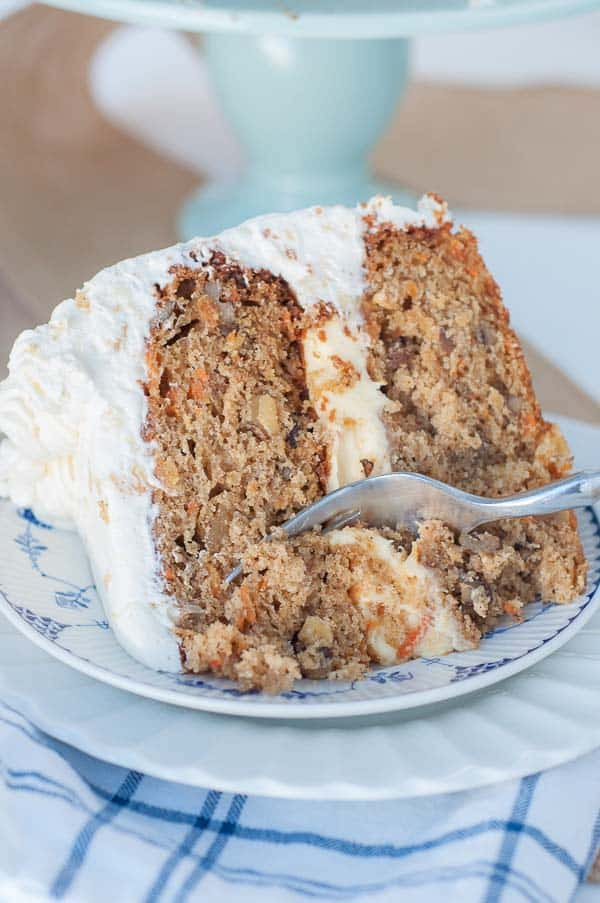A fork diving into Pineapple Carrot Cake with Fluffy Pineapple Whipped Cream Frosting