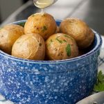 a spoon drizzling melted butter on salt potatoes