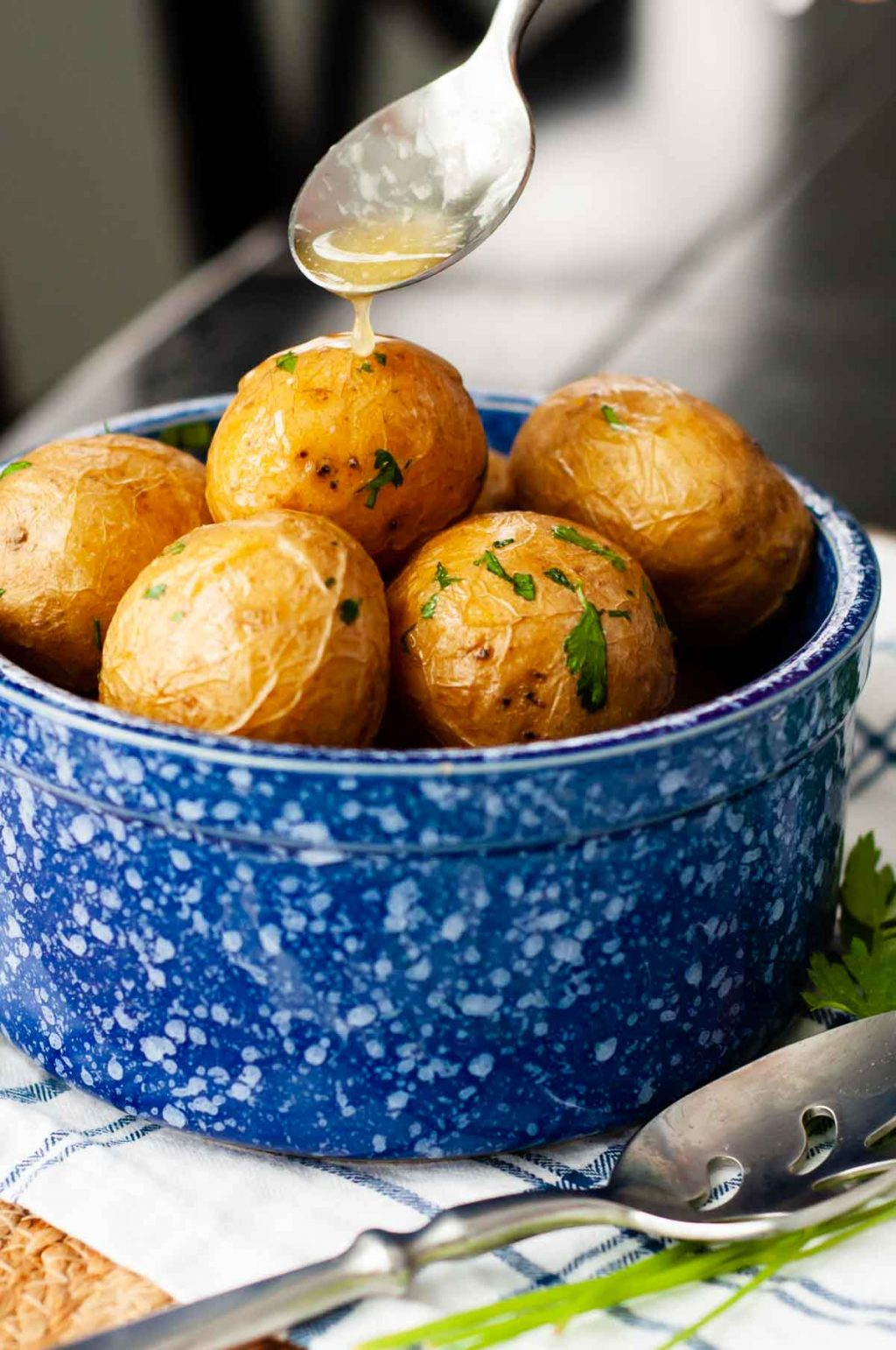 butter being spooned over a bowl of salt potatoes