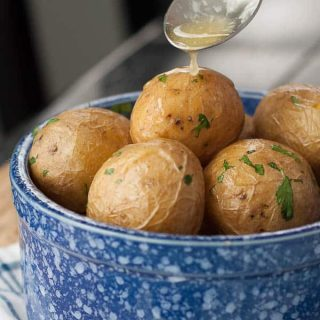A bowl of boiled salt potatoes with a spoon of melted butter being poured on top.