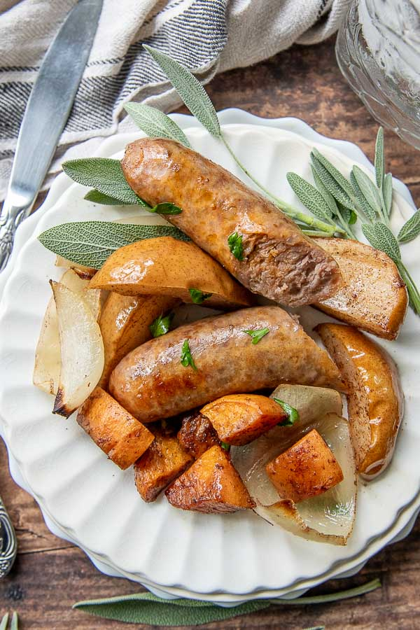 Baked Sausage dinner on a white plate with fresh sage laying next to it
