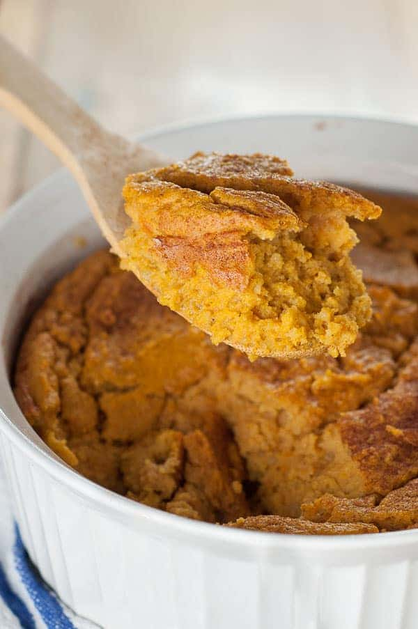 A large wooden spoon holding up a serving of Naturally Gluten Free Sweet Potato Spoon Bread