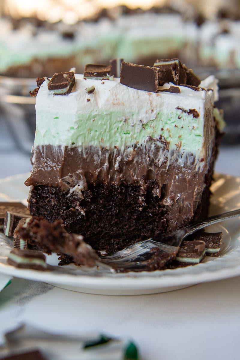 a large bite taken out of andes mint chocolate pudding poke cake with a fork resting on plate