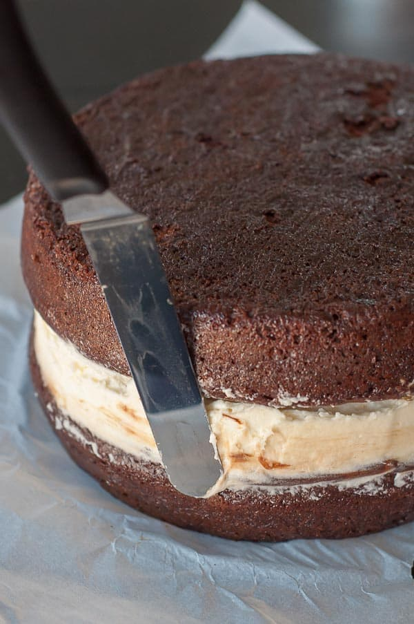 An offset spatula smoothing the filling for The caramel being made for the ganache covering Salted Chocolate Ding Dong Cake