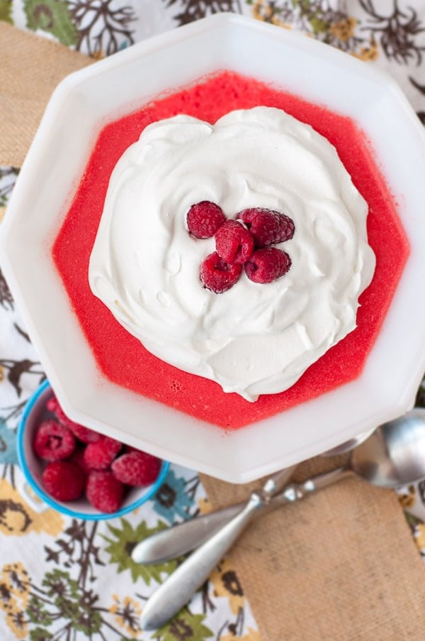 an overhead shot of jello salad in a white trifle dish with cool whip and raspberries on top