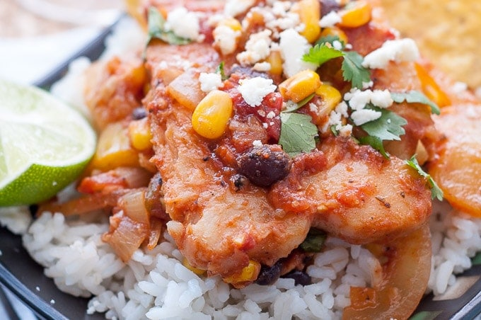 a close up shot of mexican fish recipe sitting on a bed of rice on a black plate