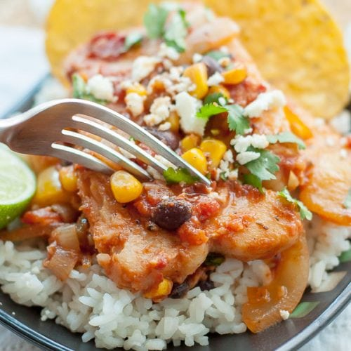 a fork about to cut into a plate of mexican fish served on rice