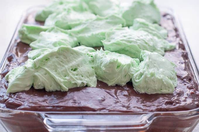 Globs of mint cream sitting on the pudding layer for Fluffy Mint Cream Chocolate Pudding Poke Cake