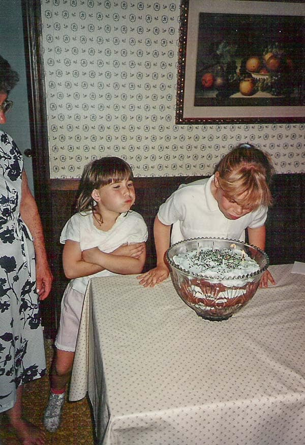 An old picture of punch bowl cake being served, which is a version of Fluffy Mint Cream Chocolate Pudding Poke Cake