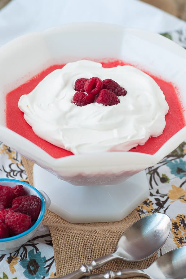 The Best Raspberry Cream Cheese Jello Salad in a large, white serving bowl with whipped topping and fresh raspberries on top