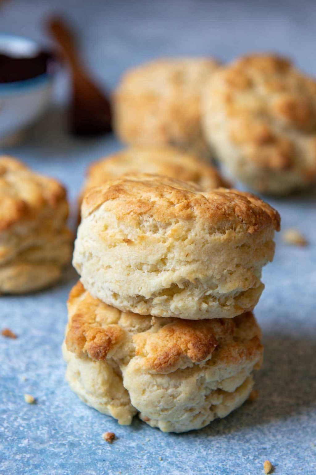 a stack of two gluten free biscuits with more biscuits laying around them