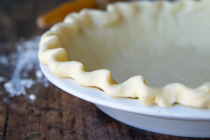a close up of gluten free pie crust in a white pie plate