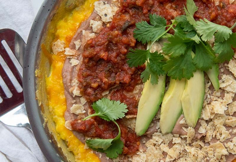 overhead shot of mexican frittata in a skillet layered with beans, chips, and salsa