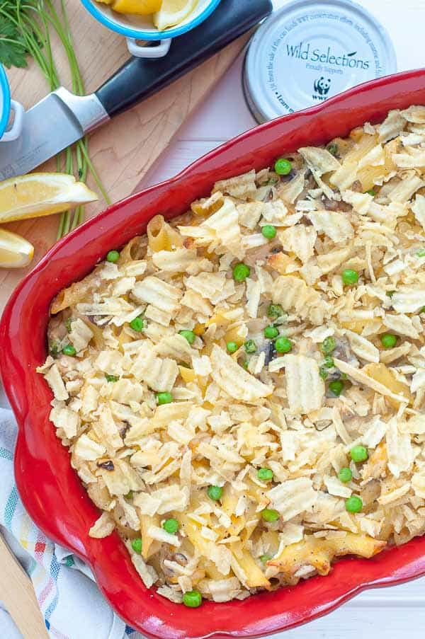 overhead shot of tuna noodle casserole in a red baking dish with cutting board and knife laying next to it