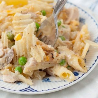 a small white plate with serving of tuna noodle casserole and fork taking a bite out to it