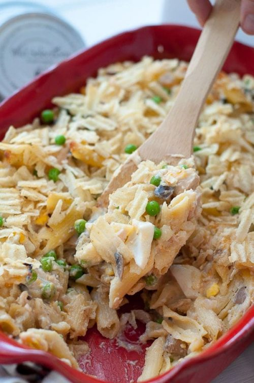 a wooden spoon scooping out a serving of tuna noodle casserole