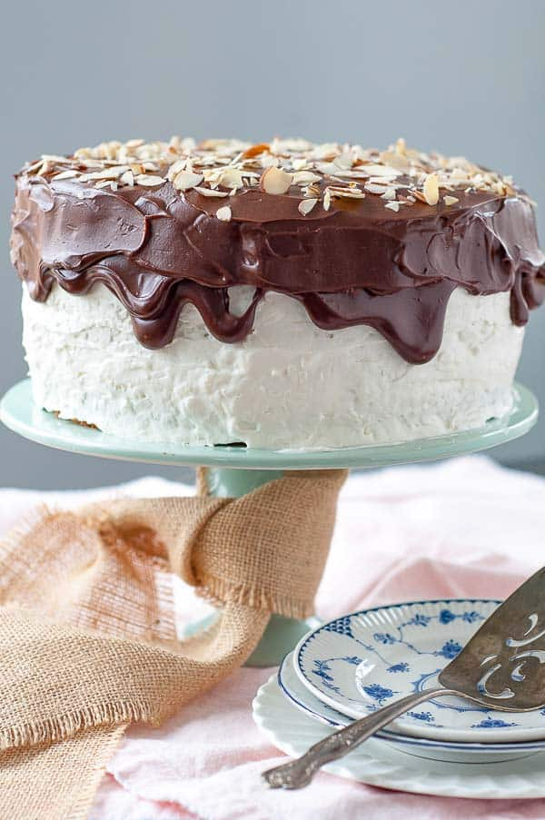 Almond Joy Cake on a green cake stand with burlap ribbon tied around base