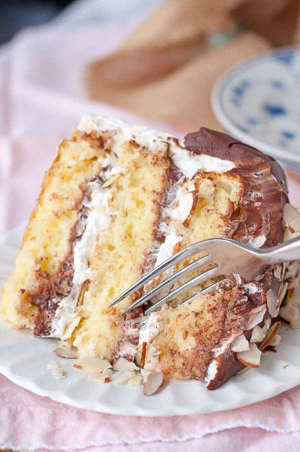 A slice of almond joy cake with a fork diving in