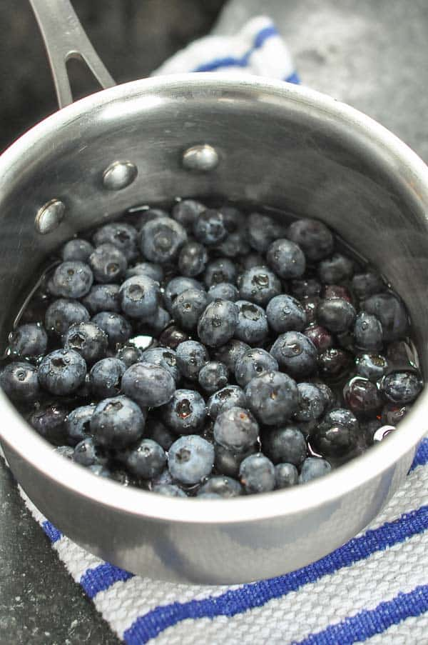 a small pot of blueberries covered with water
