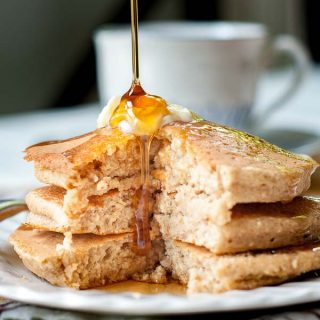 syrup being poured over a stack of flourless pancakes