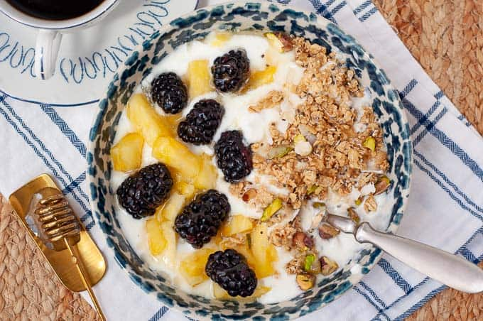 an overhead shot of a bowl of yogurt with granola, blackberries, pineapple, and granola on top