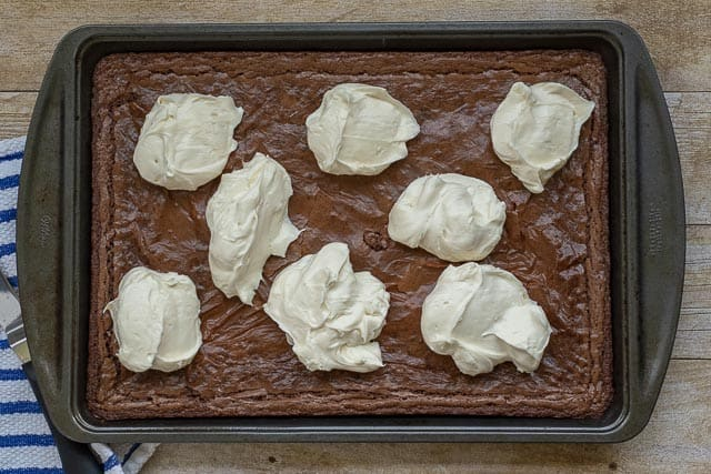 overhead shot of frosting dollops on cooled brownies