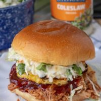 a BBQ pulled chicken sandwich on a plate with coleslaw, BBQ sauce, and grilled pineapple